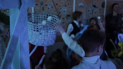 Kids throwing white balls in to basket, having fun in room with colorful lights Stock Footage
