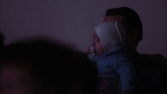 Little toddler child with soother in mouth on fathers hands in dark event room Stock Footage