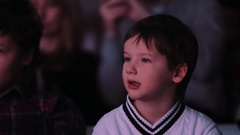 Little boy in white jumper interested looking off camera in event theatre room Stock Footage