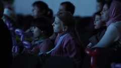 Kids with balloon animals interested looking off camera in event theatre room Arkistovideo