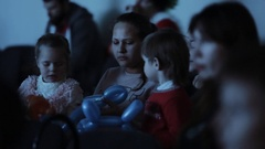 Children with balloon animals interested looking off camera in event theatre Arkistovideo