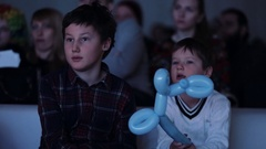 Brothers with balloon animals interested looking off camera event theatre room Arkistovideo
