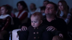 Little toddler child sitting on father lap in dark event room Stock Footage