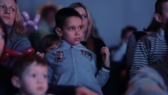 Worried boy in uninterested looking off camera event theatre room Stock Footage