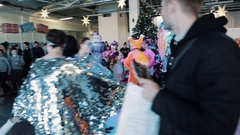 Roundelay around pine tree kids and actors dressed as christmas characters Stock Footage
