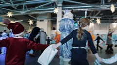 Roundelay around pine tree kids and artists dressed as christmas characters Stock Footage