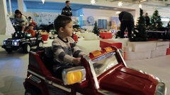 Little boys riding Battery Operated kids Cars inside shopping mall on christmas Stock Footage