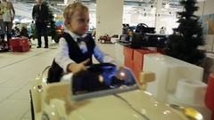 Child boys riding Battery Operated kids Cars inside shopping mall on christmas Stock Footage
