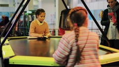 Little girls with plaids playing air hockey in shopping mall playground Stock Footage