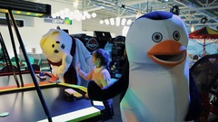 Little girls with plaids playing air hockey with penguin mascot in shopping mall Stock Footage