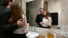 Woman put powder on face, stand at bathroom, man come and embrace her Stock Footage