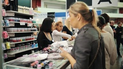 Women observe over types of nail polish and patterns at cosmetic exhibition Stock Footage