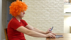 Funny guy in orange afro wig sit by table, cant choose mobile device Stock Footage