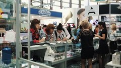 Women gathered around showcase with nail polish at cosmetic exposition Stock Footage
