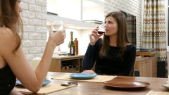 Young serious woman drink wine and speak with girlfriend sit by table at home Stock Footage