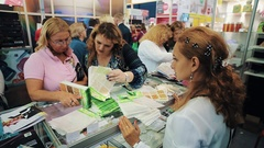 Women and manager observe colorful pattern styles over showcase at cosmetic fair Stock Footage