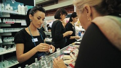 Manager showing nail polish product to customer at cosmetic beauty product fair Stock Footage