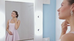 Portrait of woman with make-up looking at her reflection in mirror, fixing hair Stock Footage