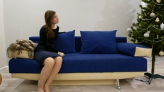 Young woman sit alone at sofa, look aside, speak with someone, Christmas tree Stock Footage