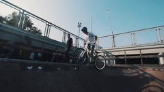 Guy in helmet on bicycle sliding on ramp in skatepark on sunny day Stock Footage