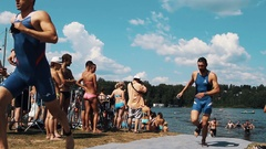 Wet athletes walk out water and start running on fabric path way. Triathlon Stock Footage