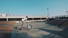 Guy in helmet on bicycle rides flips in skate park on sunny day in summertime Stock Footage