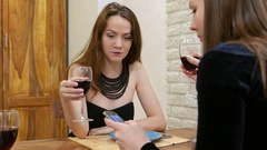 Young woman speak with friend, sitting at table with glass of wine, serious face Stock Footage