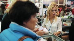 Manager talk to woman customer over nail polish display at cosmetic fair Stock Footage