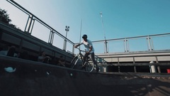 Guy in helmet on bicycle grinding on rail in skatepark on sunny day Stock Footage