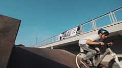 Rider in helmet on bicycle jump on ramp in skate park and clap hands behide back Stock Footage