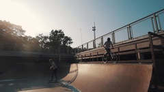 Guy in helmet on bicycle rides tricks in skate park on sunset in summertime Stock Footage