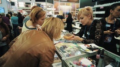Woman and manager discuss nail decorating product at cosmetic beauty showcase Stock Footage