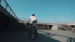 Tracking shot of guy in helmet on bicycle doing tricks in skatepark on sunny day Stock Footage