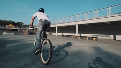 Tracking shot of boy in helmet on bicycle doing tricks in skatepark on sunny day Stock Footage