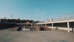 Guy in helmet on bicycle jump on ramp in skate park and clap hands behide back Stock Footage