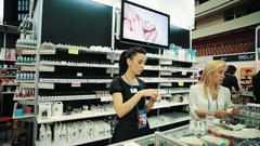 Managers at nail polish stand during cosmetic and beauty products fair Stock Footage