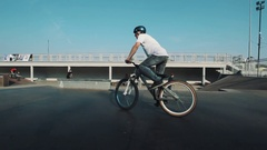 Tracking shot of guy in helmet on bicycle showing tricks in skatepark, sunny day Stock Footage