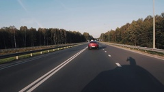 Red car changing lines on country asphalt route on sunny day in summertime Stock Footage