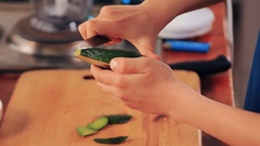 Teen hands with knife peeling half of avocado skin on kitchen cutting board Stock Footage