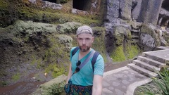 Male traveler exploring ancient Balinese temple surroundings on foot holding Stock Footage