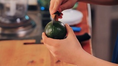 Teen hands with knife cut avocado in half and peel skin on kitchen table Stock Footage
