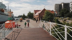 Park on waterfront covered with paving stone, people walking on sunny day Stock Footage