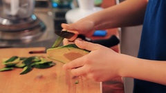 Teen arms with knife peeling half of avocado skin on kitchen table Stock Footage