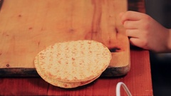 Teen hands put tortilla bread on cutting board and put souce on with spoon Stock Footage