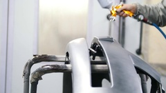 A professional car painter is painting detail of the bumper in garage by Stock Footage