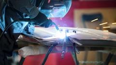 Welding industrial: worker in helmet repair detail in car service Stock Footage
