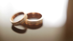 Golden wedding rings on mirror glasses table - one lies top of another Stock Footage