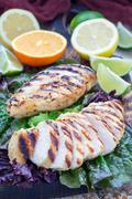 Grilled chicken breast in citrus marinade on salad leaves and wooden cuttin.. Stock Photos