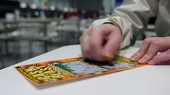 Scratching lottery ticket inside shopping mall food court area Stock Footage