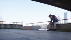 4K One man sits waiting for someone whilst using his phone, with space for text Stock Footage